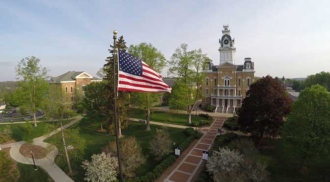 Hillsdale College campus aerial view of the main plaza with an American flag prominently displayed in the foreground. Walkways between buildings frame the grass-covered lawn and there are numerous trees with bright green foliage scattered across the landscape.