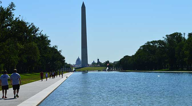 A photo of the Washington Monument in Washington, DC. The angel is taken from the far end of the Reflecting Pool with the monument slightly off-center, trees on either side of the pool are in full, green summer foliage and the sky is bright blue.