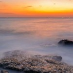 Long exposure seascape during blue hour sunset with rocks as foreground. Nature composition.