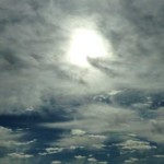 A mostly-cloudy sky with high altitude, scattered clouds. The sun partially shows through the clouds and there are patches of clear, dark blue sky.