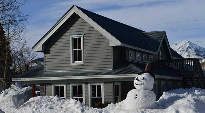 A gray two-story home set in a winter landscape. Snow is piled up in front of the house with a snowman in the right, front foreground, mixed foliage trees on the left and a snow-covered mountain in the background with blue sky overhead.