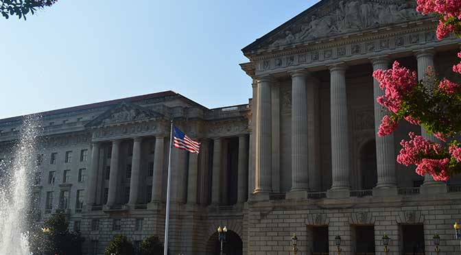 A large granite building in classical architechture, with large columns in front. There is a flowering trees in the right foreground and an American flag on a pole at left-center. Spray from a water fountain is seen at the far left foreground and blue sky is overhead.