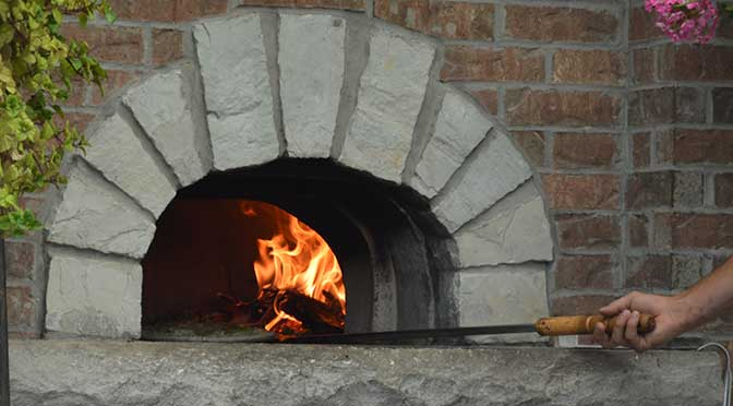 The flames of a brick and stone oven are pictured though the open mouth of the oven. A hand holds a large oven spatula on the right side, with green foliage in the upper left corner and pink flowers in the upper right corner of the picture.