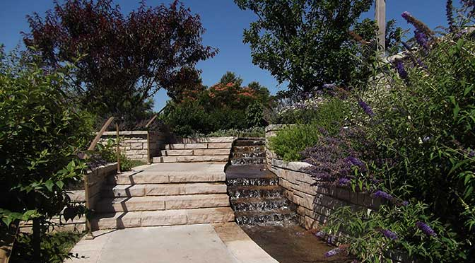 A stone walkway leads to stone steps curving upwards from left bottom to right upper frame of the picture. There is a water spillway on the right side of the walkway, and various plants and shrubs line either side. beneath a clear, blue sky.