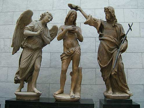 Three white marble statues on black marble pedestals representing Jesus being baptized by John the Baptist, with an angel looking on.